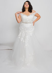 Gorgeous bridal gowns for all body shapes: plus size, curvy, or petite brides. Try on our wedding dresses at home. Size 0-30. Comfortable. Convenient. Fun. Lace or satin. Mermaid or A-line. From the off the shoulder neckline down to the tulle trumpet, this dress has something to admire at every inch.  The beautiful ivory lace pattern of this skirt draws down into a dramatic, romantic tulle trumpet that will figure-flatter and add interest.