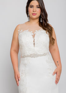 Gorgeous bridal gowns for all body shapes: plus size, curvy, or petite brides. Try on our wedding dresses at home. Size 0-30. Comfortable. Convenient. Fun. Lace or satin. Mermaid or A-line. The illusion top and tailored silhouette of the skirt are the perfect balance between romantic and sleek. This lace illusion top shows a hint of skin, while keeping your dress in place so you are left without a worry. The lace detailing reaching down the sides of this trumpet skirt adds romance.