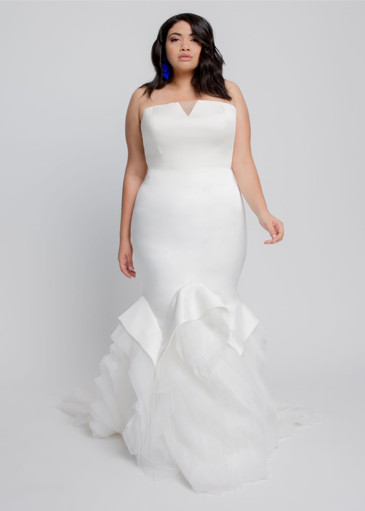 Gorgeous bridal gowns for all body shapes: plus size, curvy, or petite brides. Try on our wedding dresses at home. Size 0-30. Comfortable. Convenient. Fun. Lace or satin. Mermaid or A-line.  This clean crepe gown in Ivory, adds drama with a mermaid organza ruffle hem. The tulle V draws eye down to a figure-flattering silhouette. Billowing layers of organza ruffles in matching Ivory complete a modern classic bridal look. An elegant lace-up back assists in a great fit and added detail.