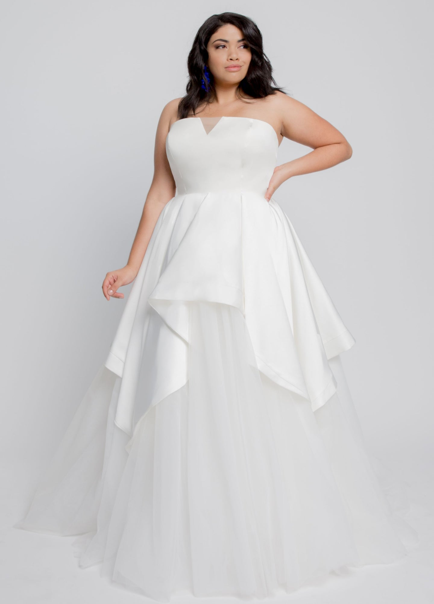 Gorgeous bridal gowns for all body shapes: plus size, curvy, or petite brides. Try on our wedding dresses at home. Size 0-30. Comfortable. Convenient. Fun. Lace or satin. Mermaid or A-line.  The Knightly Dress features an elegant A line satin dress with light and airy ball gown. The satin strapless bustier features a flattering tulle V panel. The assymetric detail in front adds a modern twist to a classic style creating clean and elegant lines. Tulle layers create an illusion as if walking on a cloud.
