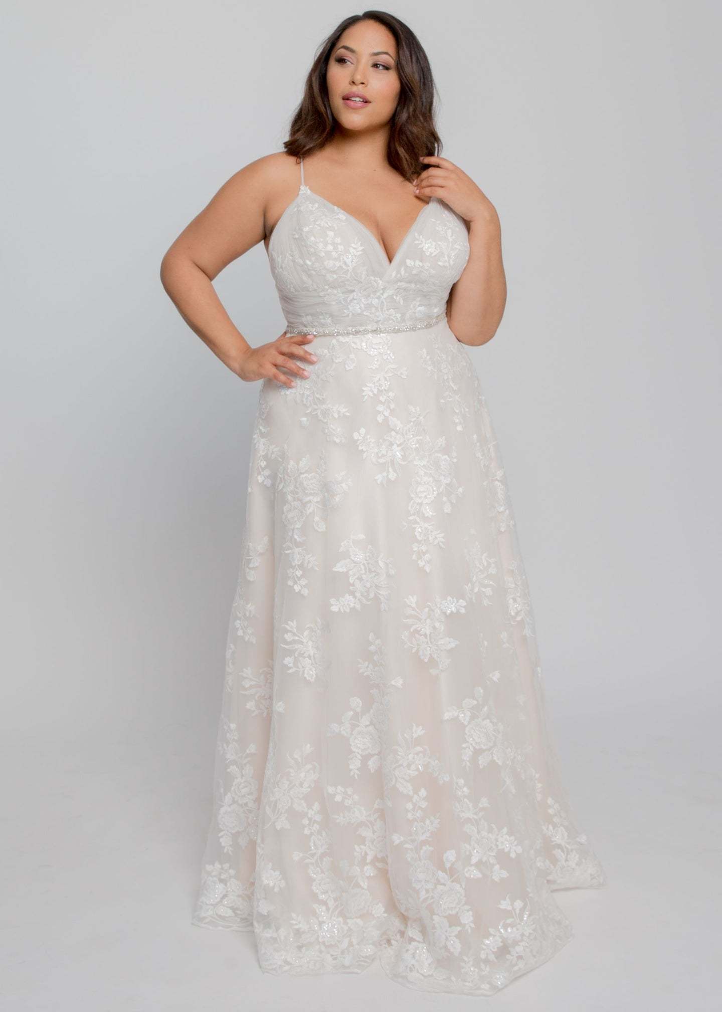 Gorgeous bridal gowns for all body shapes: plus size, curvy, or petite brides. Try on our wedding dresses at home. Size 0-30. Comfortable. Convenient. Fun. Lace or satin. Mermaid or A-line.  This gown features enchanting lace with a sultry V neckline and flattering A line skirt. This lace is soft to the touch and features lovely roses covering the dress from neckline to hem. Delicate, nude lining brings out details of the soft ivory lace that falls beautifully from the waist.