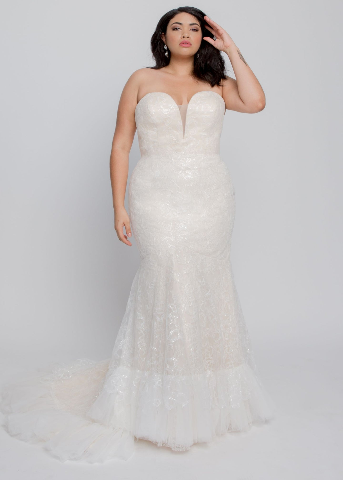 Gorgeous bridal gowns for all body shapes: plus size, curvy, or petite brides. Try on our wedding dresses at home. Size 0-30. Comfortable. Convenient. Fun. Lace or satin. Mermaid or A-line. The Beverly Gown features a champagne lining with lovely beaded, floral lace in a classic gown with sweetheart neckline and fitted trumpet skirt with a chapel train and Tulle detail on hem. The neckline adds a splash of modernity with its plunging V covered with a champagne tulle panel.