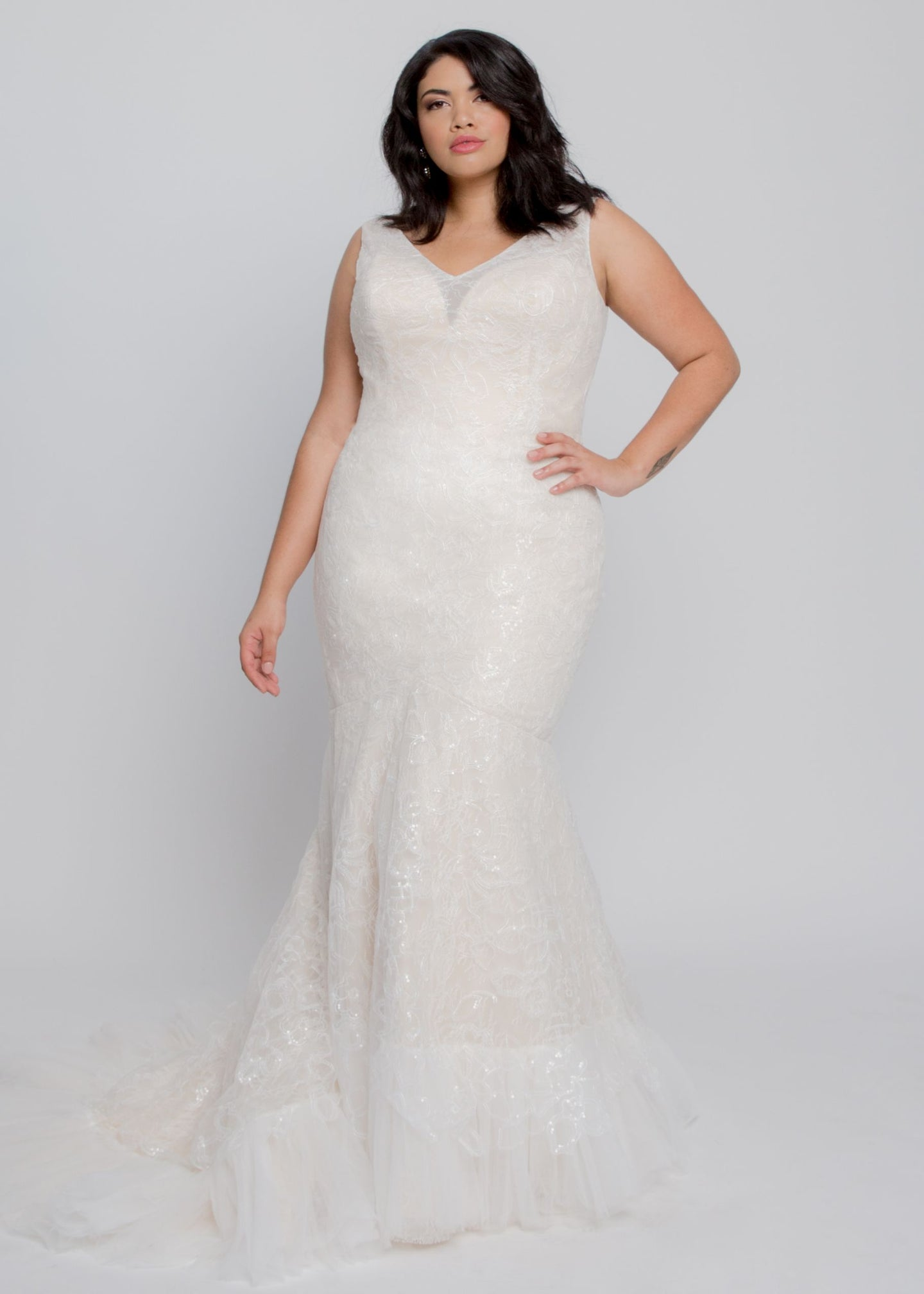 Gorgeous bridal gowns for all body shapes: plus size, curvy, or petite brides. Try on our wedding dresses at home. Size 0-30. Comfortable. Convenient. Fun. Lace or satin. Mermaid or A-line. The Violet Gown combines classic V neckline and trumpet skirt with a modern floral lace over a Champagne lining. Clean and open neckline in back is sure to wow along with the chapel train lined in tulle. Beading on the lace adds understated sparkle to this elegant gown.