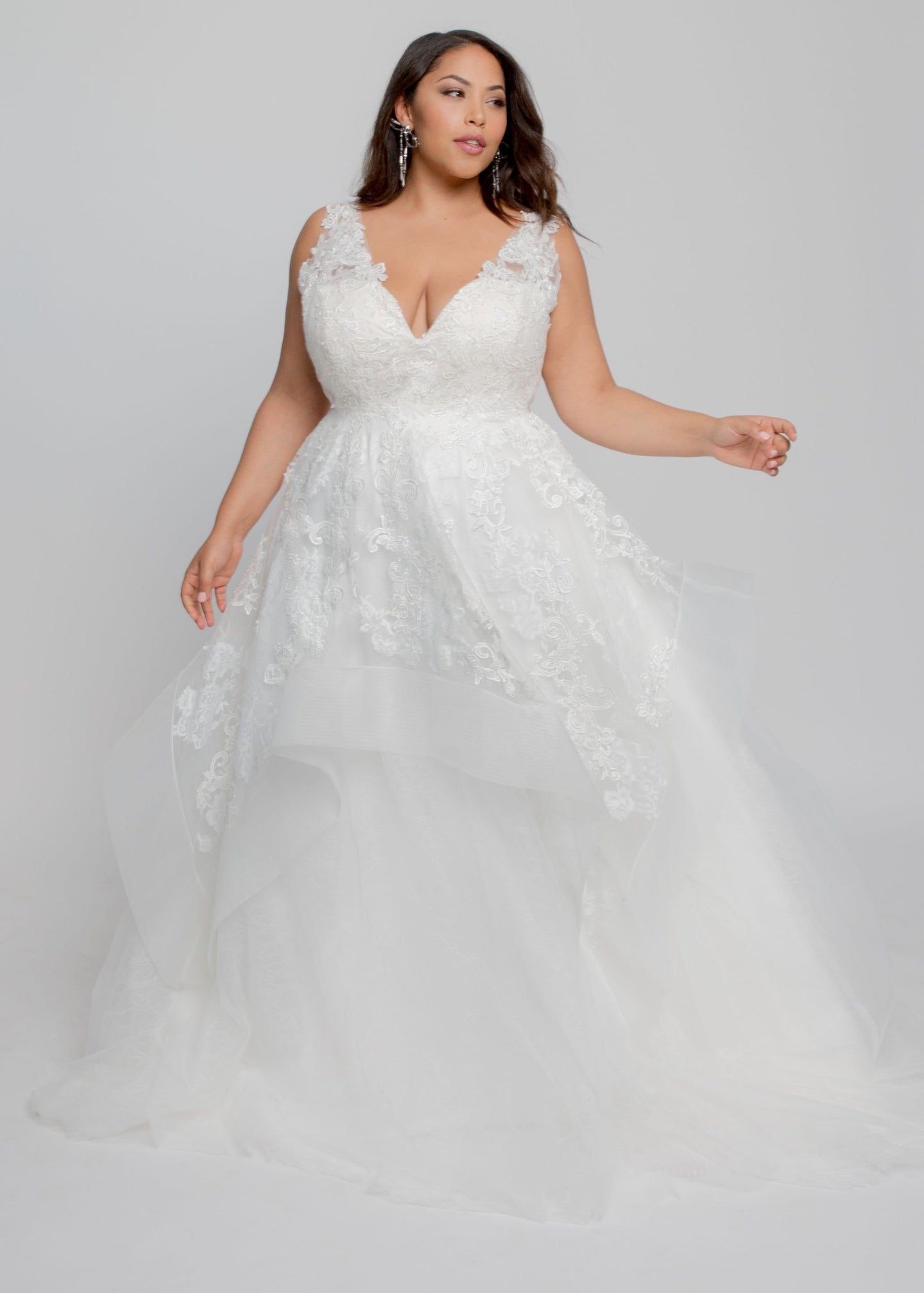 Gorgeous bridal gowns for all body shapes: plus size, curvy, or petite brides. Try on our wedding dresses at home. Size 0-30. Comfortable. Convenient. Fun. Lace or satin. Mermaid or A-line.  Fulfill your lace dreams with this gown featuring a stunning lace-lined V neckline and layered lace and tulle skirt. Applique details are delicately placed from the tulle sleeves to the horsehair hems on this skirt.