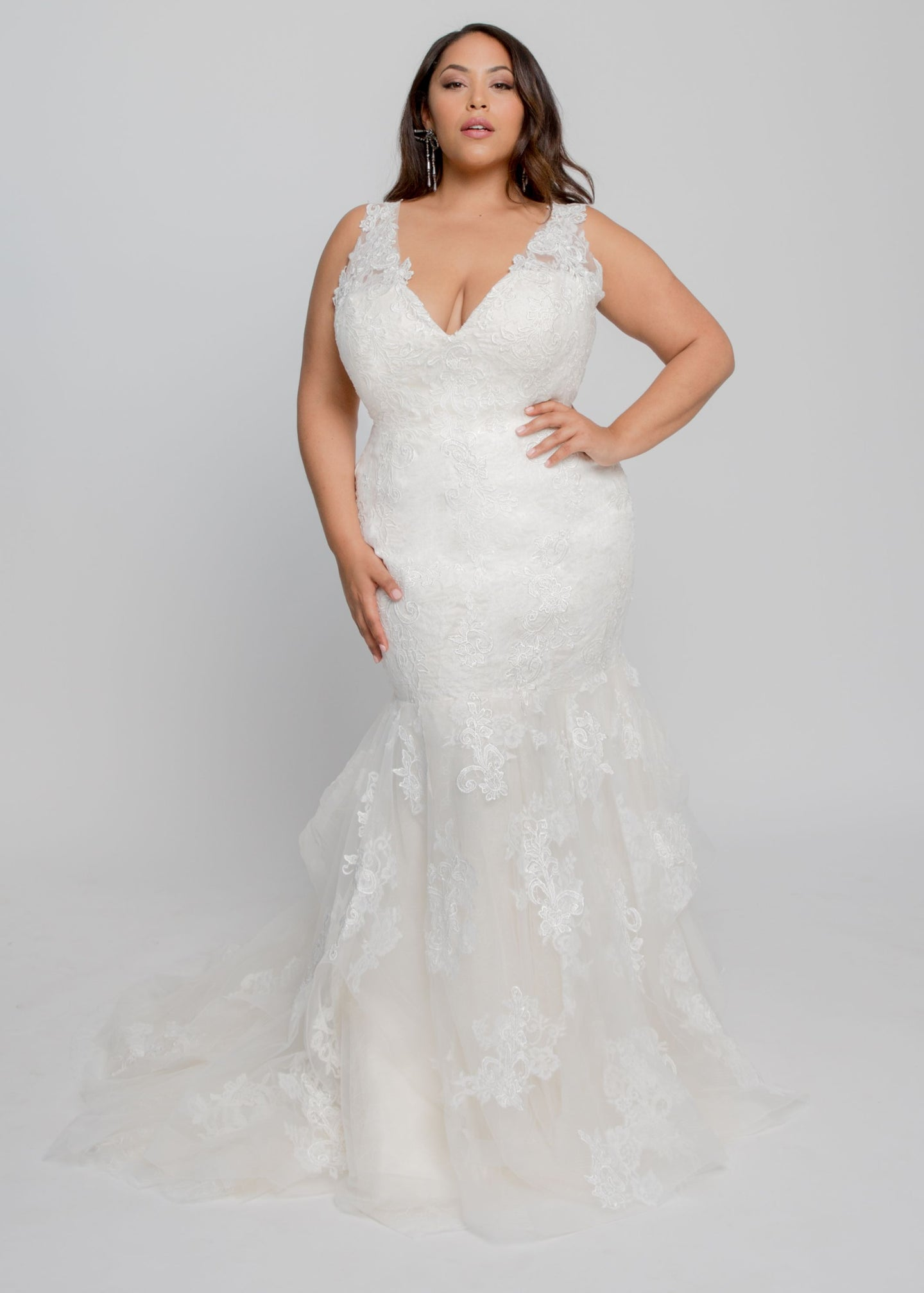 Gorgeous bridal gowns for all body shapes: plus size, curvy, or petite brides. Try on our wedding dresses at home. Size 0-30. Comfortable. Convenient. Fun. Lace or satin. Mermaid or A-line.  Fulfill your lace dreams with this gown featuring a stunning lace-lined V neckline and layered lace and tulle skirt. This figure hugging shape shows off your curves and features a billowy tulle layered skirt. The applique details and layered laces and champagne tulle lead to an ethereal chapel train