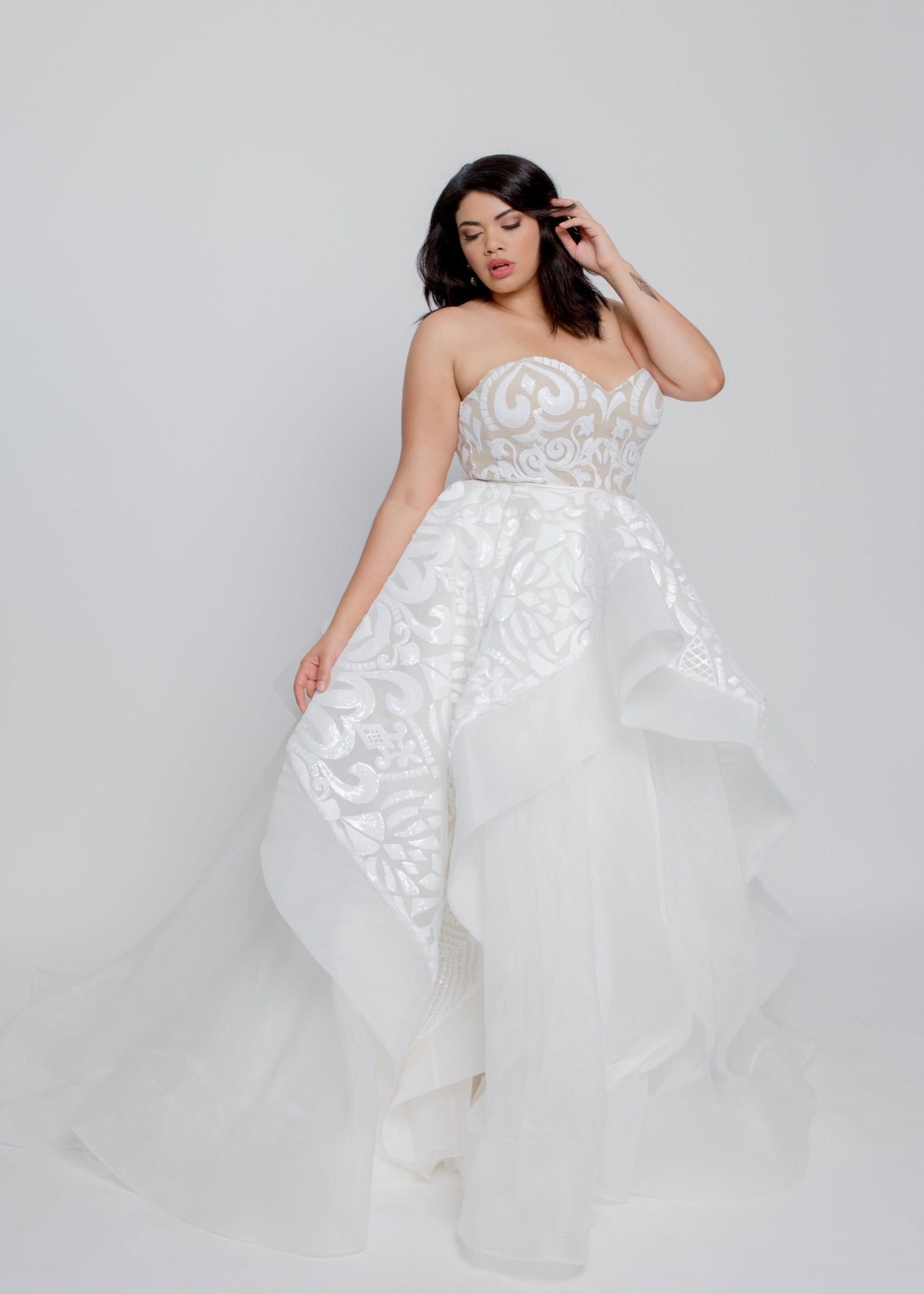 Gorgeous bridal gowns for all body shapes: plus size, curvy, or petite brides. Try on our wedding dresses at home. Size 0-30. Comfortable. Convenient. Fun. Lace or satin. Mermaid or A-line. This intricately detailed sequin-embellished dress is a unique, on-trend ball gown that you will admire long after your wedding day. Beautifully beaded sweetheart bustier leads to layered skirt with horsehair trimmed organza, providing great volume and staying power.