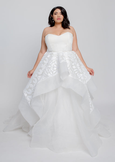 Gorgeous bridal gowns for all body shapes: plus size, curvy, or petite brides. Try on our wedding dresses at home. Size 0-30. Comfortable. Convenient. Fun. Lace or satin. Mermaid or A-line.  The Bella Gown features a simple and chic sweetheart top with beaded detail ball gown skirt in ivory organza. The horsehair trim on this beaded skirt gives this dress volume and staying power. The gown also features a sweep train for added flair.