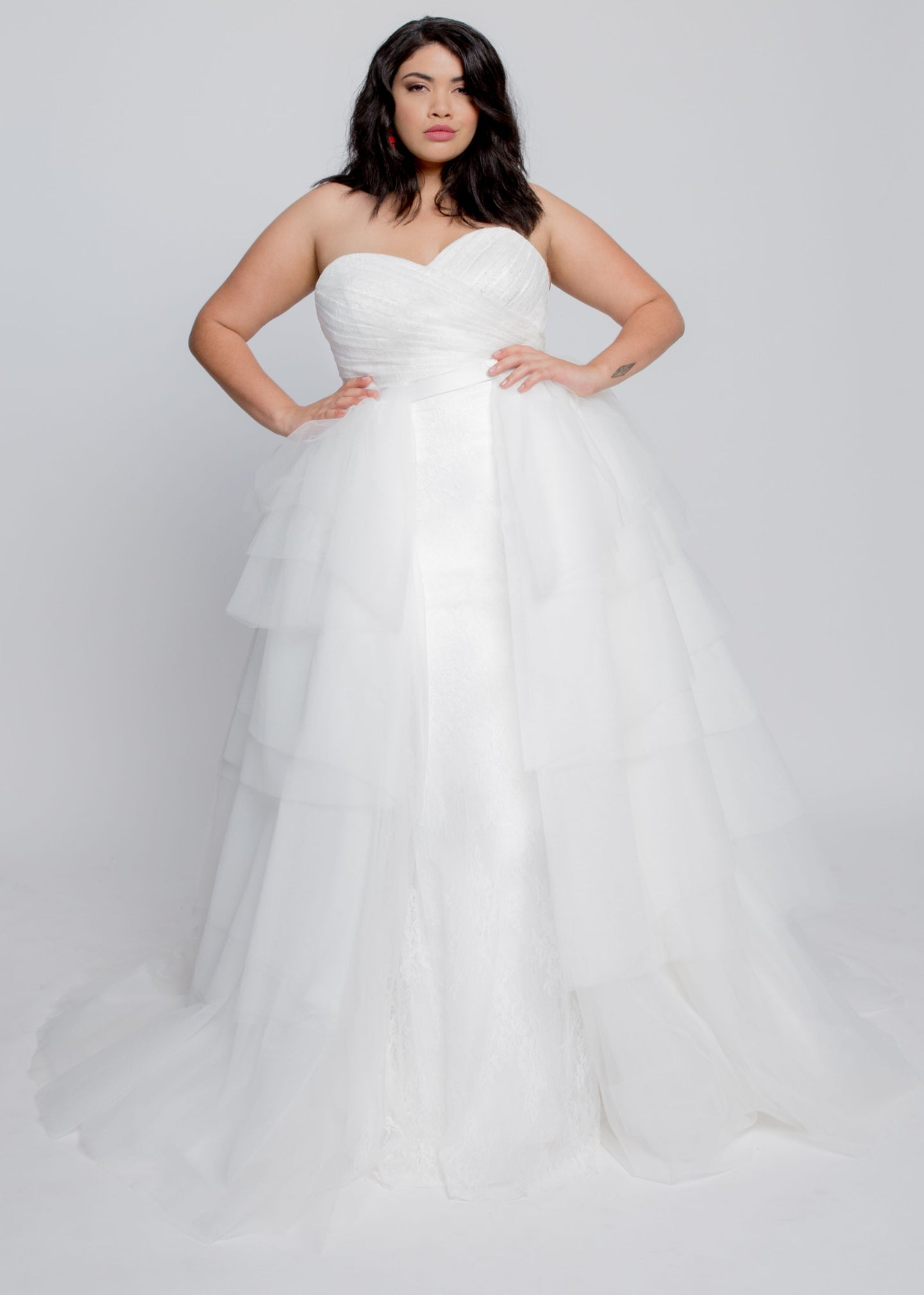 Gorgeous bridal gowns for all body shapes: plus size, curvy, or petite brides. Try on our wedding dresses at home. Size 0-30. Comfortable. Convenient. Fun. Lace or satin. Mermaid or A-line.  Make any dress into a ball gown silhouette with layers of soft tulle in the Pimerly Overskirt. Easily attaches in the front and open enough to show off your favorite gown. Features a sweep train and pairs well with a line or trumpet styles.
