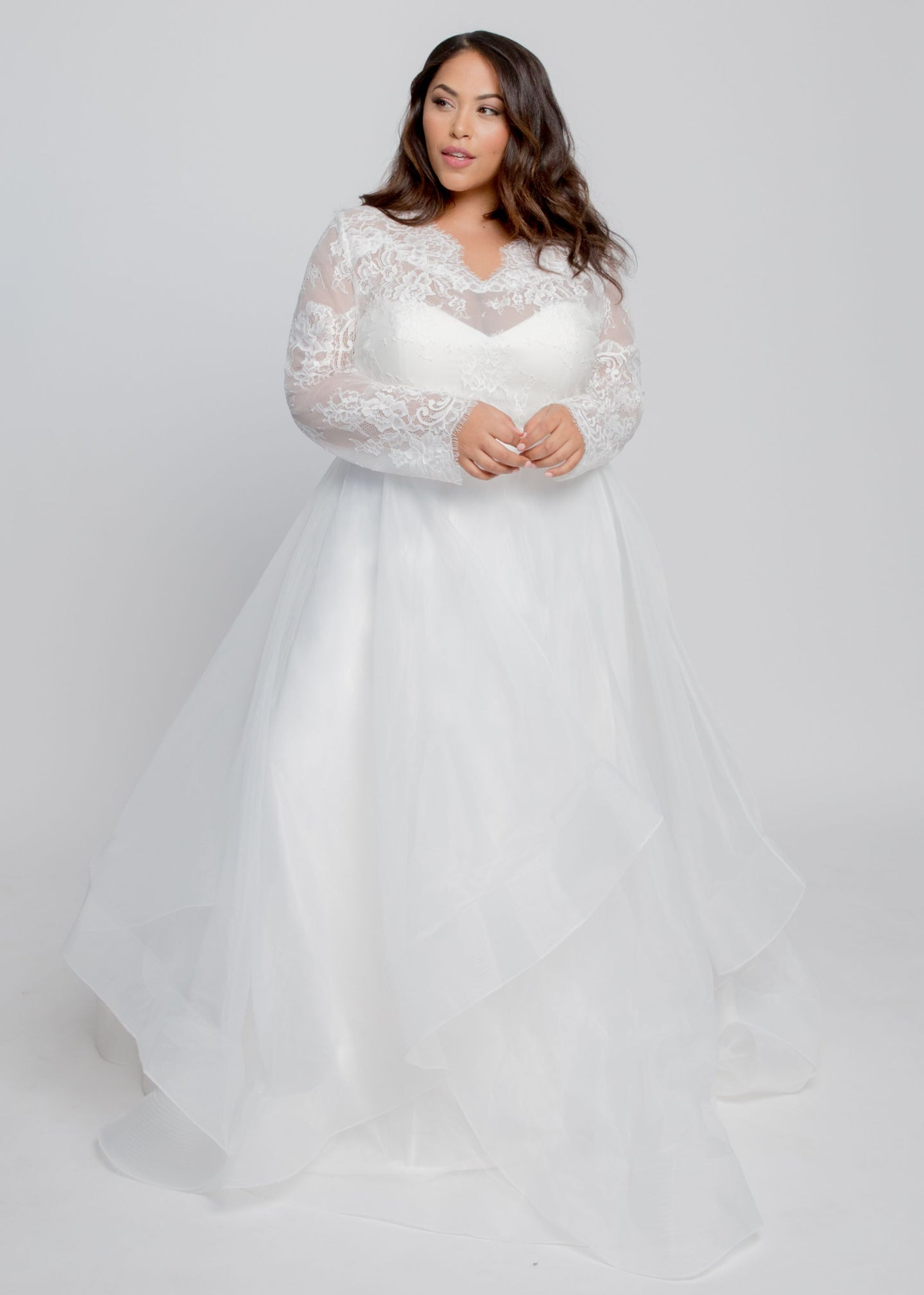 Gorgeous bridal gowns for all body shapes: plus size, curvy, or petite brides. Try on our wedding dresses at home. Size 0-30. Comfortable. Convenient. Fun. Lace or satin. Mermaid or A-line. The layers create a pretty illusion and give you the option to have sleeves or go strapless. The ivory lace topper features a detailed v neck and custom fitted long sleeves. Horsehair on the hem gives the skirt dramatic flair and accentuates your waist.