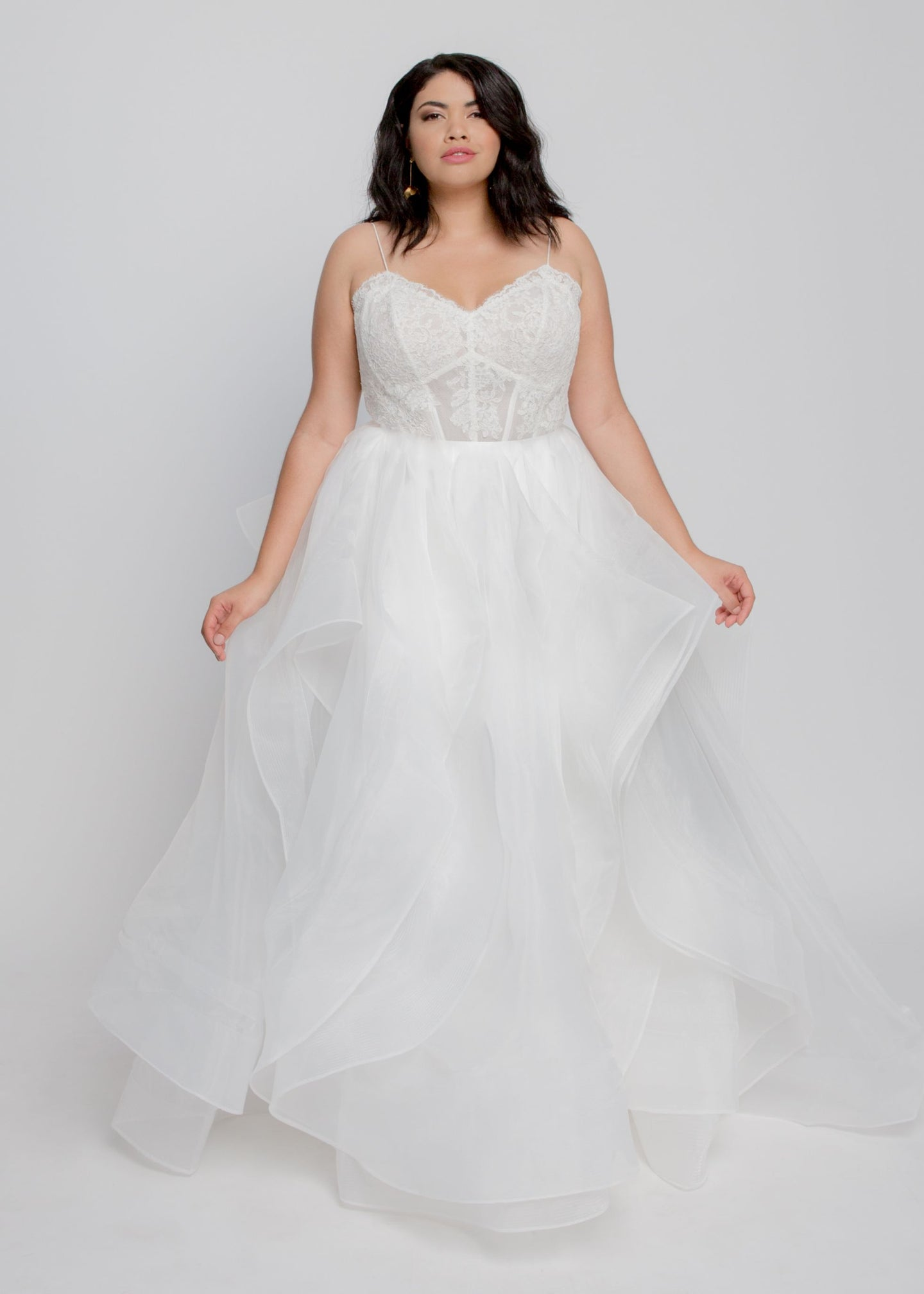 Gorgeous bridal gowns for all body shapes: plus size, curvy, or petite brides. Try on our wedding dresses at home. Size 0-30. Comfortable. Convenient. Fun. Lace or satin. Mermaid or A-line. The structured bustier offers beautiful lace with support that shows with sultry spaghetti straps. The flowing organza layers cascade beautifully and horsehair lined hems ensure they stay voluminous all day.