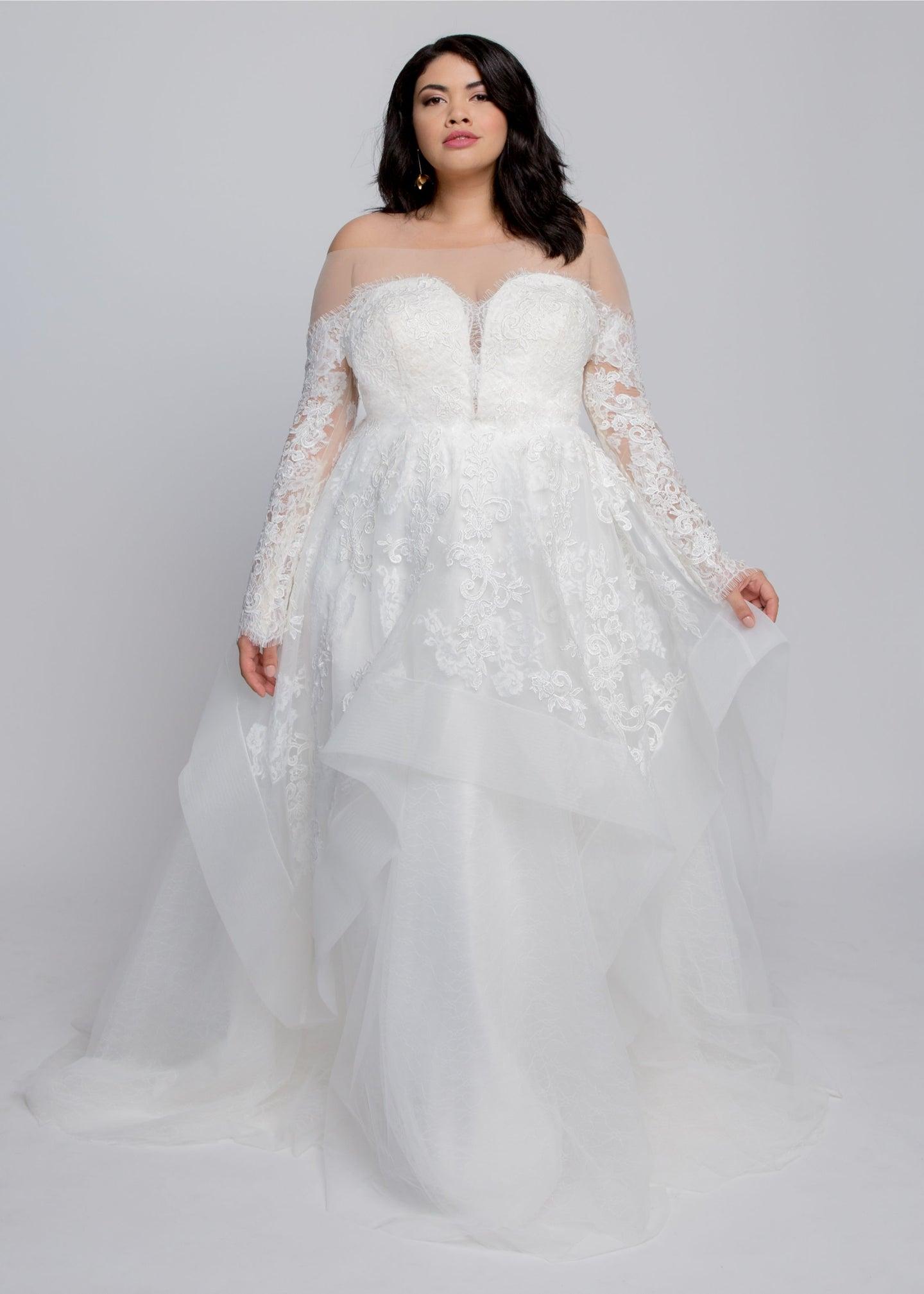 Gorgeous bridal gowns for all body shapes: plus size, curvy, or petite brides. Try on our wedding dresses at home. Size 0-30. Comfortable. Convenient. Fun. Lace or satin. Mermaid or A-line.  The Emmy Gown will allow you to glide down the aisle in soft and gorgeous layers of tulle and romance. The illusion off the shoulder silhouette and lace is a perfect pairing that will keep you feeling secure, comfortable, and beautiful. The layered lace and tulle of this ball gown skirt adds an ethereal statement.