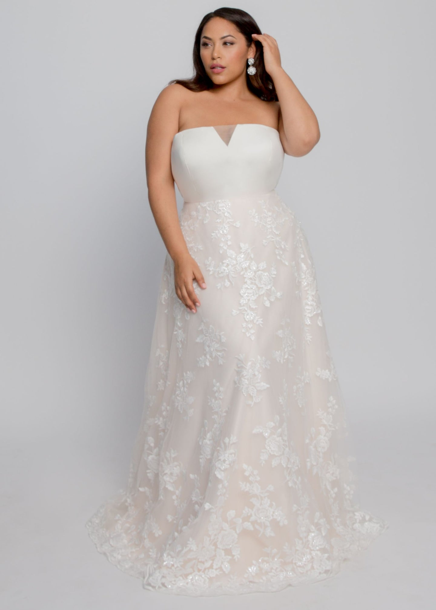 Gorgeous bridal gowns for all body shapes: plus size, curvy, or petite brides. Try on our wedding dresses at home. Size 0-30. Comfortable. Convenient. Fun. Lace or satin. Mermaid or A-line. Straight across neckline with lunging tulle panel adds a modern touch to gorgeous lace over an A line skirt. Blooming lace cascades over the blush lining to the gathered tulle hem and elegant hem.