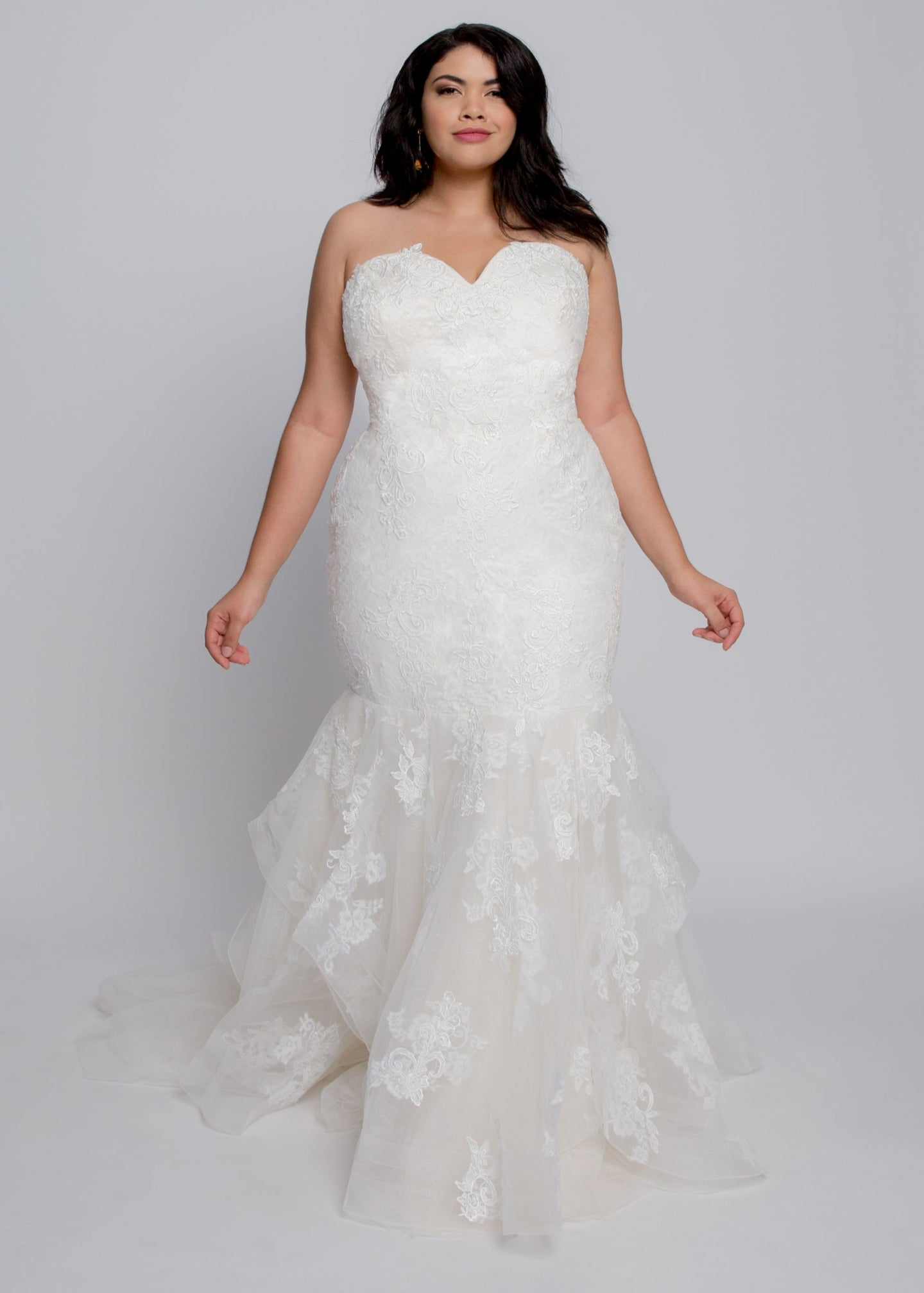Gorgeous bridal gowns for all body shapes: plus size, curvy, or petite brides. Try on our wedding dresses at home. Size 0-30. Comfortable. Convenient. Fun. Lace or satin. Mermaid or A-line. The romantic Elena Gown will flatter your curves with its sweetheart lace neckline and figure hugging mermaid skirt. Layers of ivory lace over champagne tulle feature a hint of illusion and romance. Glide down the aisle with the layers of horsehair lined, and appliqued tulle with a beautiful chapel lace train.