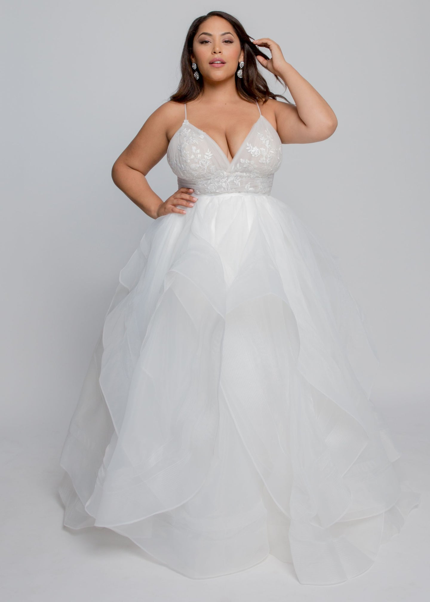 Gorgeous bridal gowns for all body shapes: plus size, curvy, or petite brides. Try on our wedding dresses at home. Size 0-30. Comfortable. Convenient. Fun. Lace or satin. Mermaid or A-line.  This gown features enchanting lace with a sultry V neckline and flowing organza skirt with horsehair hem. This lace is soft to the touch and features lovely roses to the pleated waist detail. Sultry spaghetti straps add something special to this modern and statement ball gown.