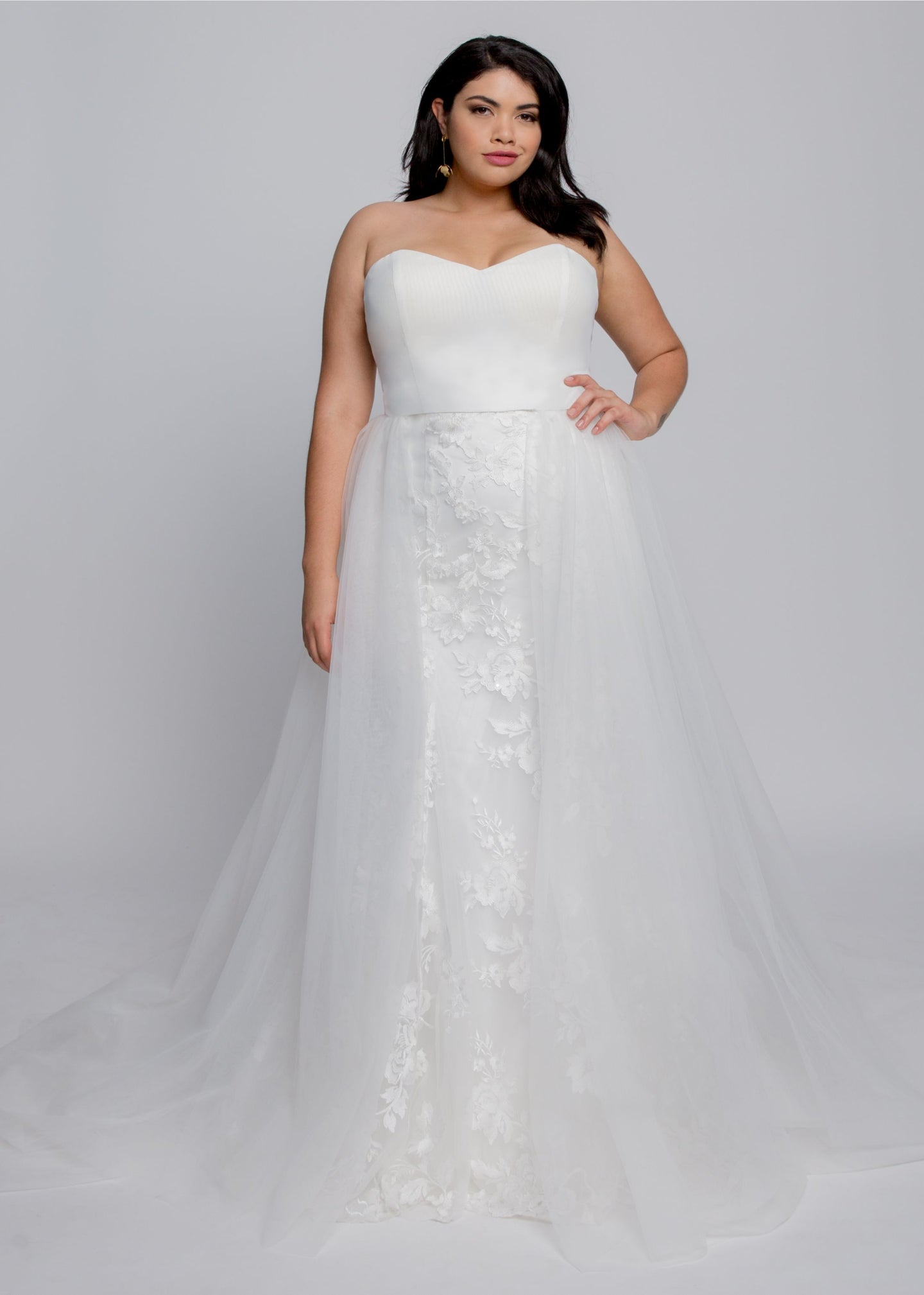 Gorgeous bridal gowns for all body shapes: plus size, curvy, or petite brides. Try on our wedding dresses at home. Size 0-30. Comfortable. Convenient. Fun. Lace or satin. Mermaid or A-line.  A classic sweetheart bustier combines with ethereal lace to create a classic wedding day look. The satin bustier and trumpet skirt bring classic elegance that is also very flattering. Floral lace in ivory over tulle add to the skirt.
