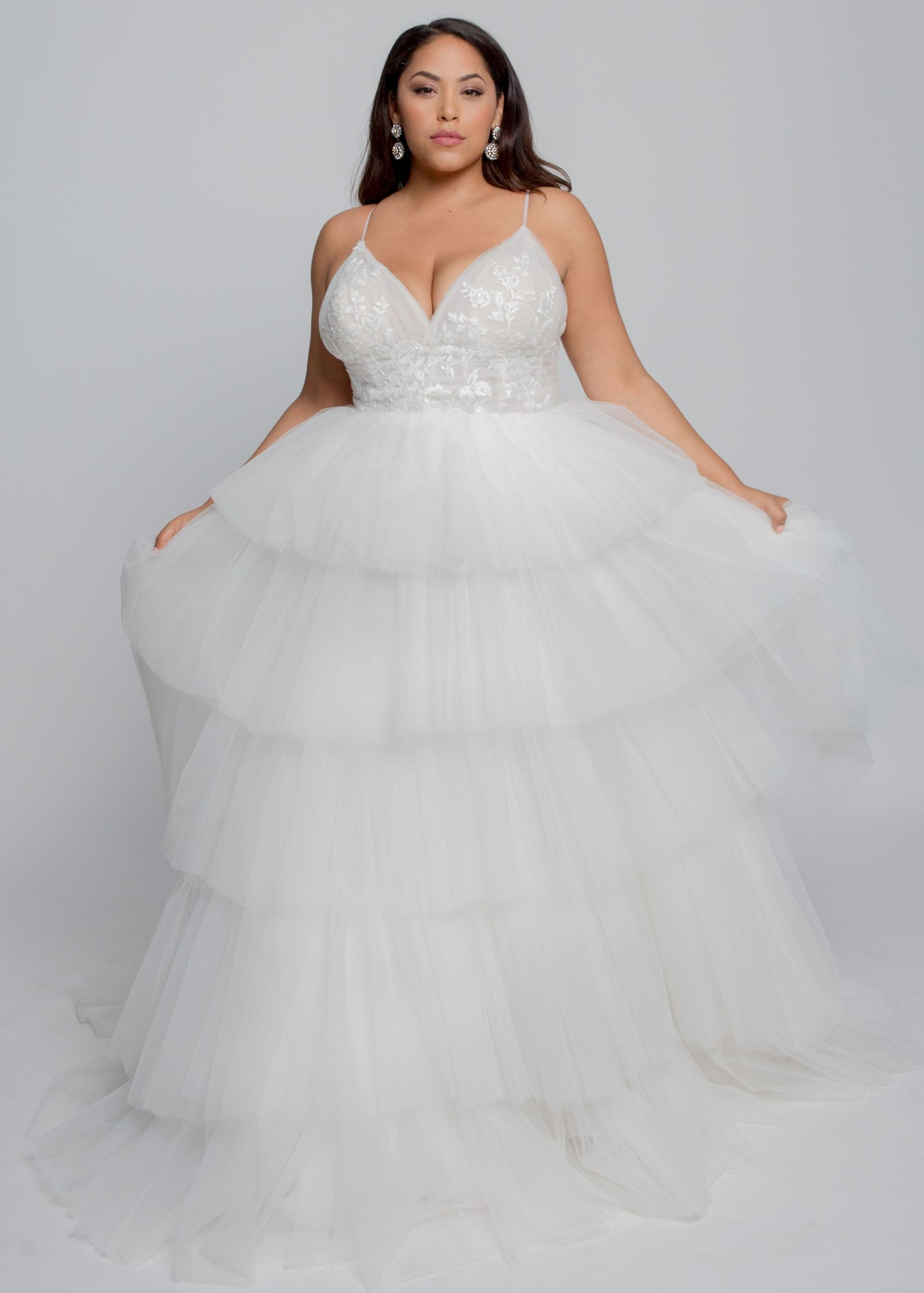 Gorgeous bridal gowns for all body shapes: plus size, curvy, or petite brides. Try on our wedding dresses at home. Size 0-30. Comfortable. Convenient. Fun. Lace or satin. Mermaid or A-line.  The romantic Hannah Gown features beautiful blush lace with tulle tiers and thin, sultry tulle straps. The V neckline combines with the blush lining is sure to flatter. Pleating at the waist adds definition and juxtaposes the ethereal tulle skirt.