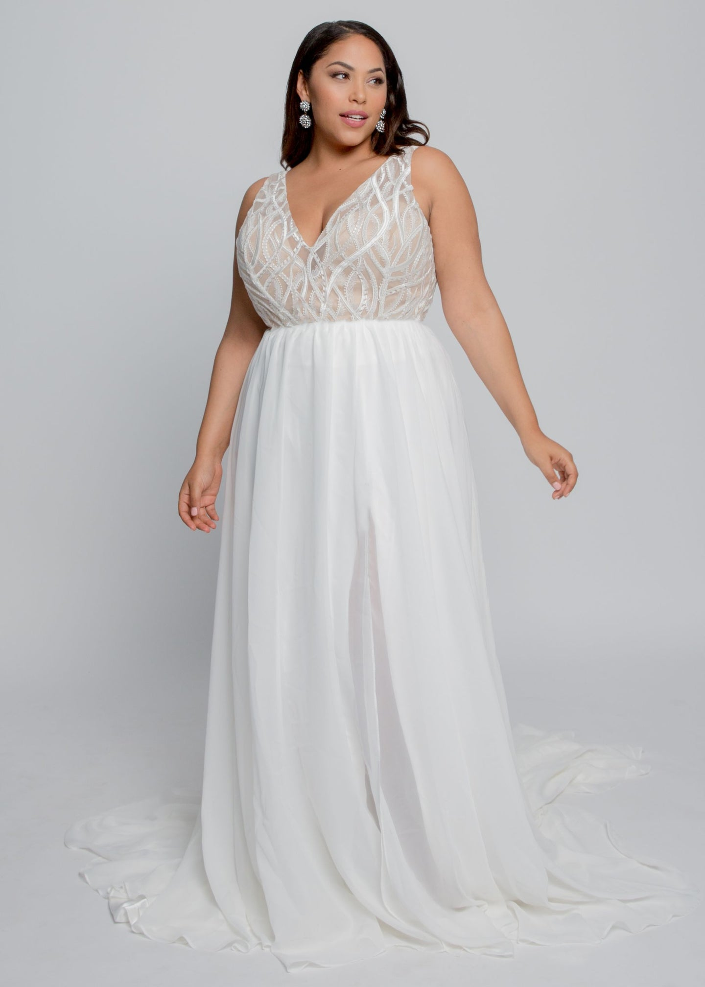 Gorgeous bridal gowns for all body shapes: plus size, curvy, or petite brides. Try on our wedding dresses at home. Size 0-30. Comfortable. Convenient. Fun. Lace or satin. Mermaid or A-line. This gown was made for the modern bride with its unique embroidered tulle V neck with ivory vines and understated beading combined with an airy chiffon skirt. The side slit in the front will allow for easy movement and a flowing skirt.