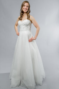 Gorgeous bridal gowns for all body shapes: plus size, curvy, or petite brides. Try on our wedding dresses at home. Size 0-30. Comfortable. Convenient. Fun. Lace or satin. Mermaid or A-line. Be the perfect picture of ethereal beauty with the Kaniko Gown with its airy A line skirt and lace detailed sweetheart top has snaps that allow you to customize even further by adding lace sleeves.The tulle A-Line skirt offers a soft volume for increased interest and romance as you glide through your wedding.