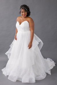 Gorgeous bridal gowns for all body shapes: plus size, curvy, or petite brides. Try on our wedding dresses at home. Size 0-30. Comfortable. Convenient. Fun. Lace or satin. Mermaid or A-line. The sharp v-neckline and layered skirt are so breathtaking that they will leave people talking about your dress for years to come. This shining tulip top gives a soft edge and securely hugs the body, making it the perfect combination of secure and sexy. Horsehair tulle tiered skirt that comes alive with every movement.