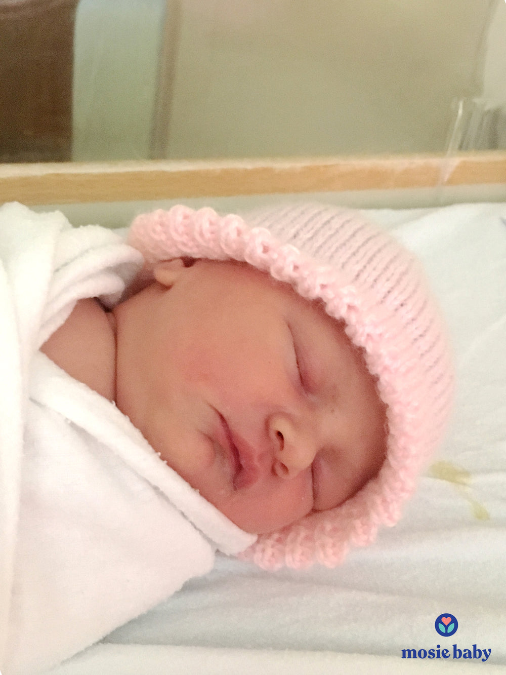 newborn baby with a pink hat