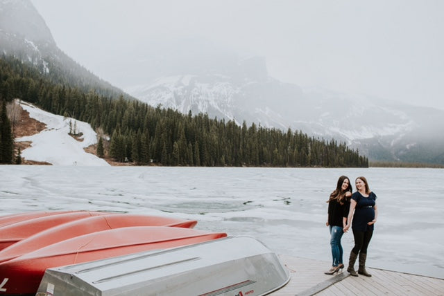 Lesbian couple holding hands on a boat dock in the mountains