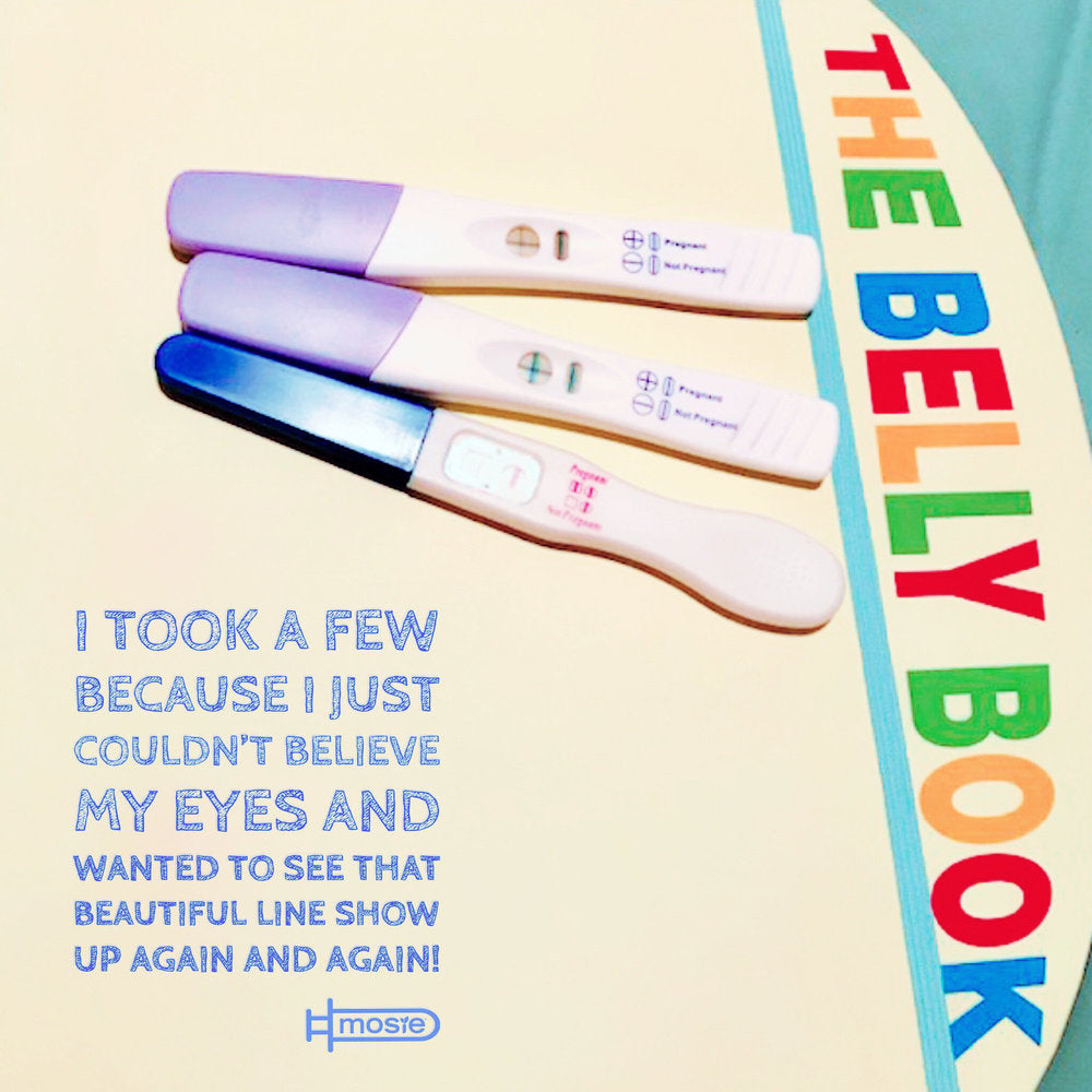 "three positive pregnancy tests on top of ""The Belly Book"" from a Mosie user"