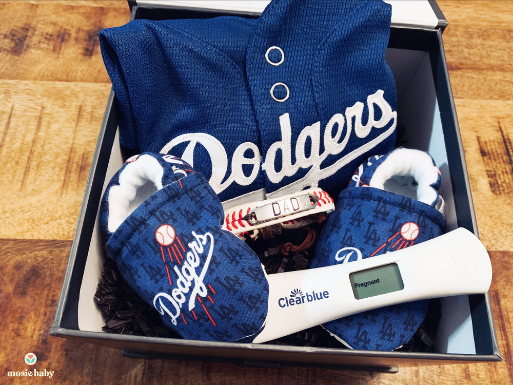 positive pregnancy test inside of a dodgers themed announcement gift box for dad