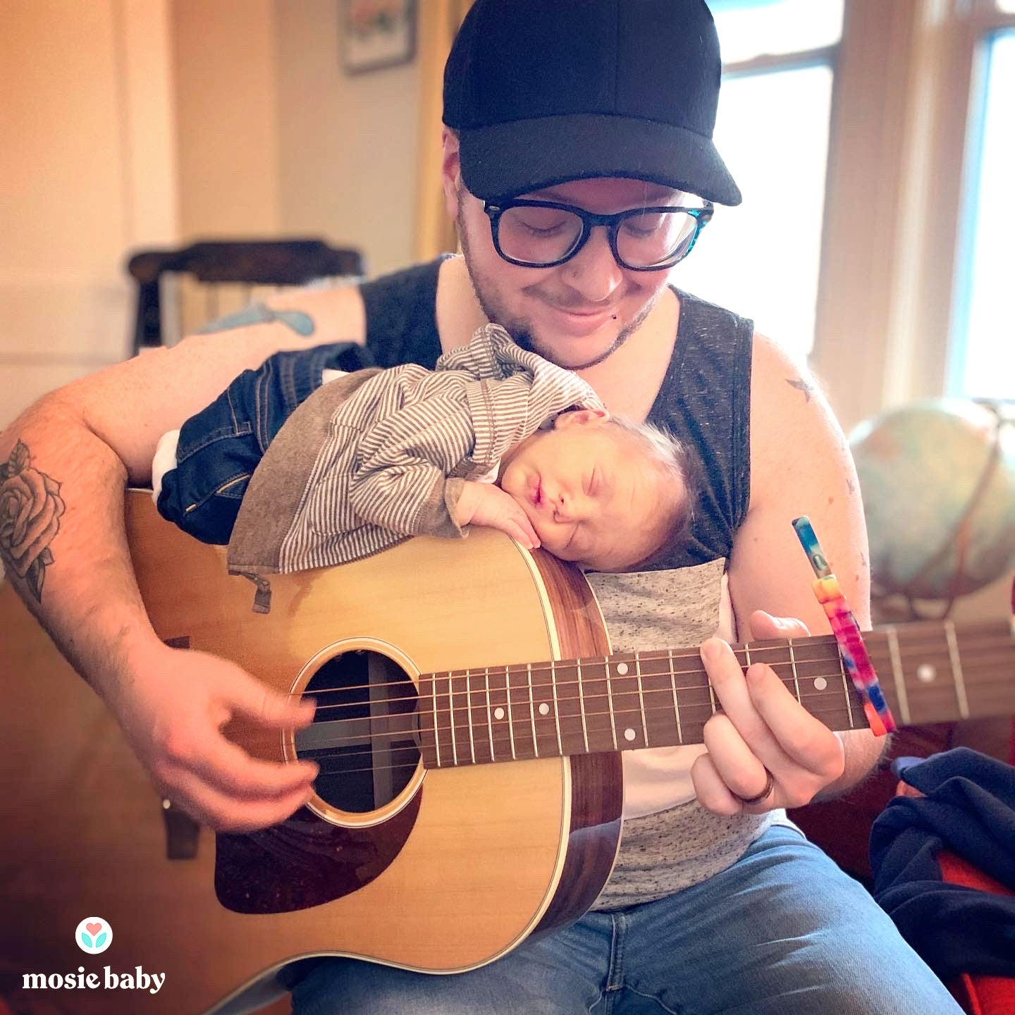 Mosie Dad playing the guitar with baby