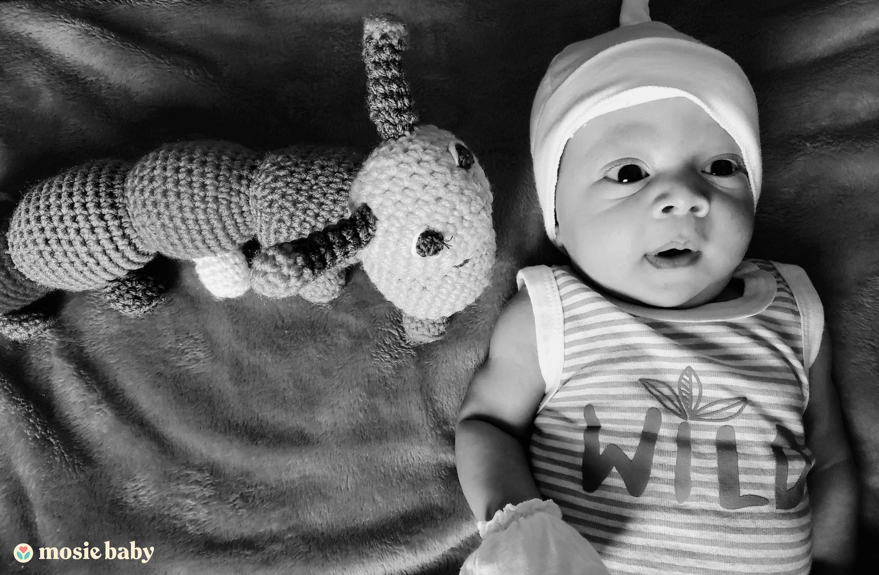 Black and white photo of a baby with a toy stuffed animal