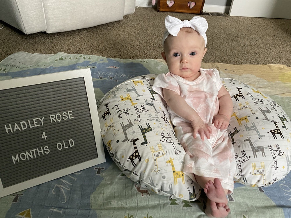"""Mosie Baby Hadley Rose sits up and smiles against a baby pillow and next to a sign that reads """"Hadley Rose, 4 months old."""""""