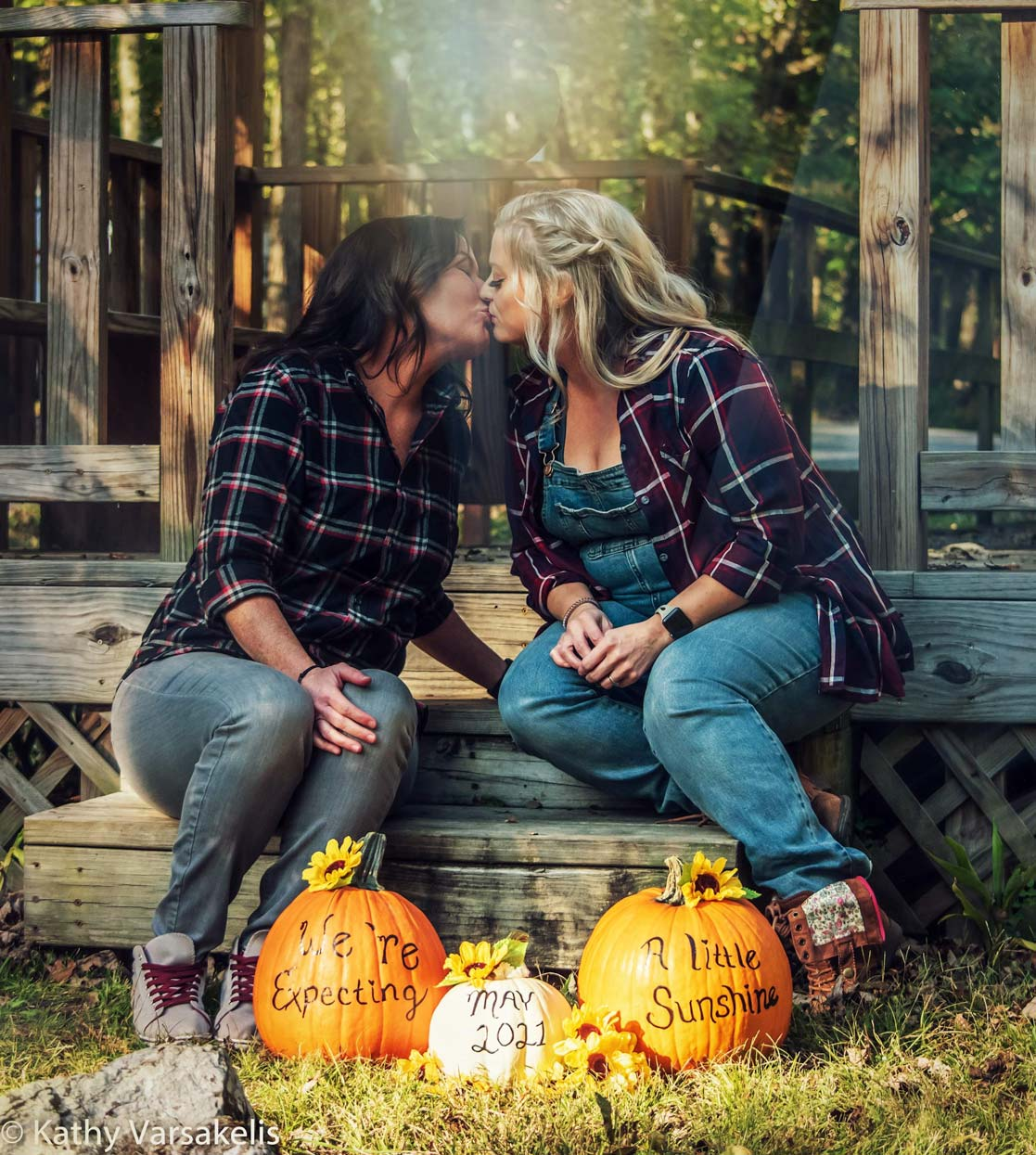 Wife and Wife dressed in flannel kissing above their baby announcement written on pumpkins.