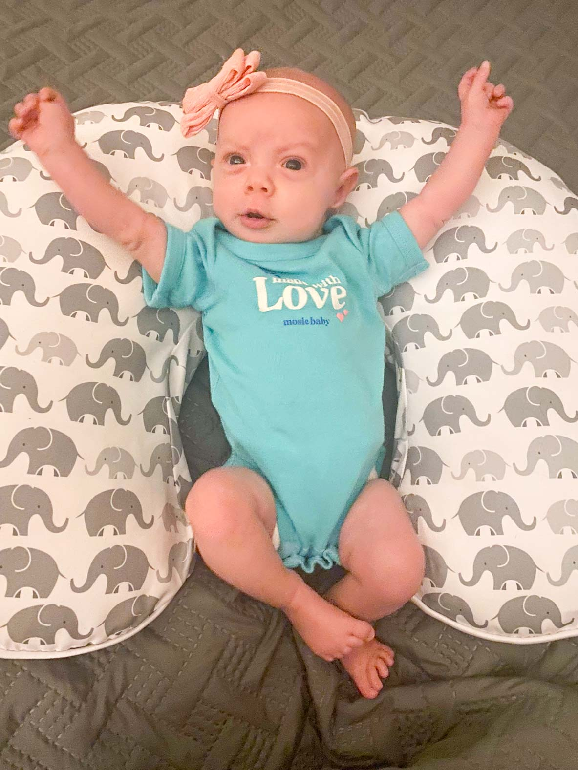 Baby girl in Mosie Baby onesie laying on elephant patterned pillow with her arms outstretched