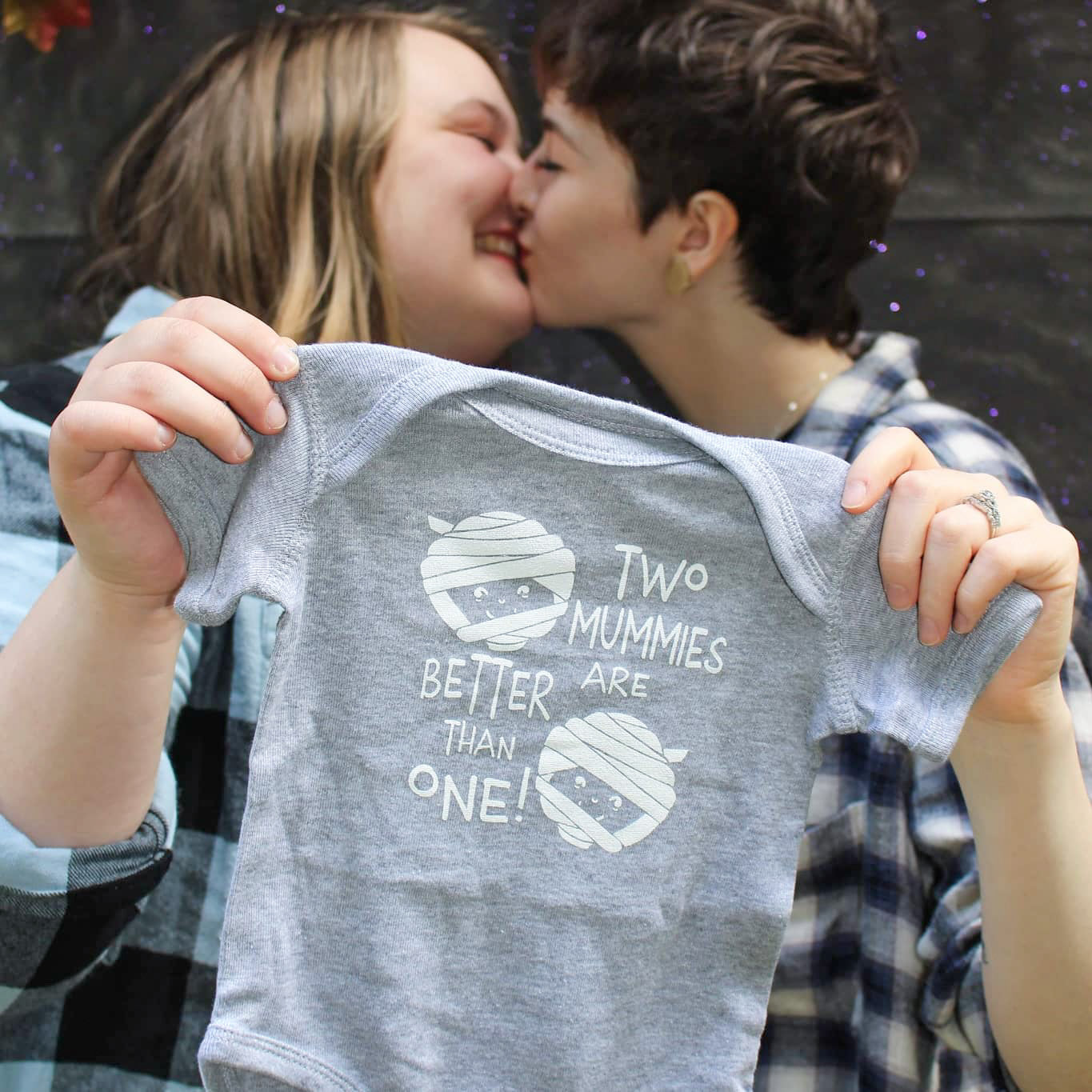 Couple kissing and holding a onesie that says two mummies are better than one.