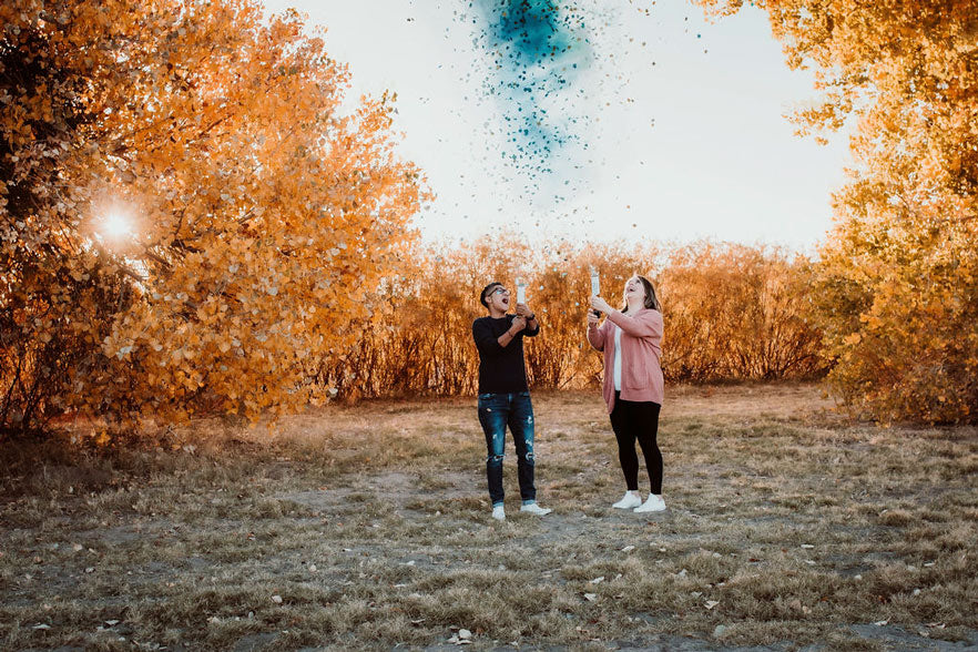 Two mamas-to-be are arms up in celebration with confetti in front of orange trees