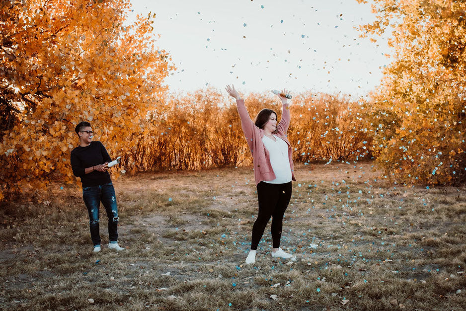 A women on the left holds a confetti cannon towards her wife, standing with arms up in celebrations in front of orange trees