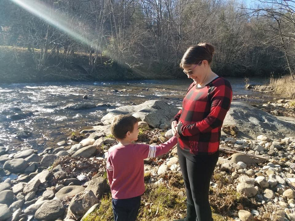 pregnant mom with her son by a river
