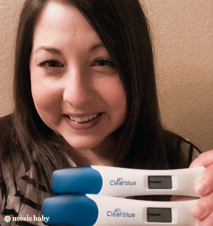 Mosie mama holding two positive pregnancy tests