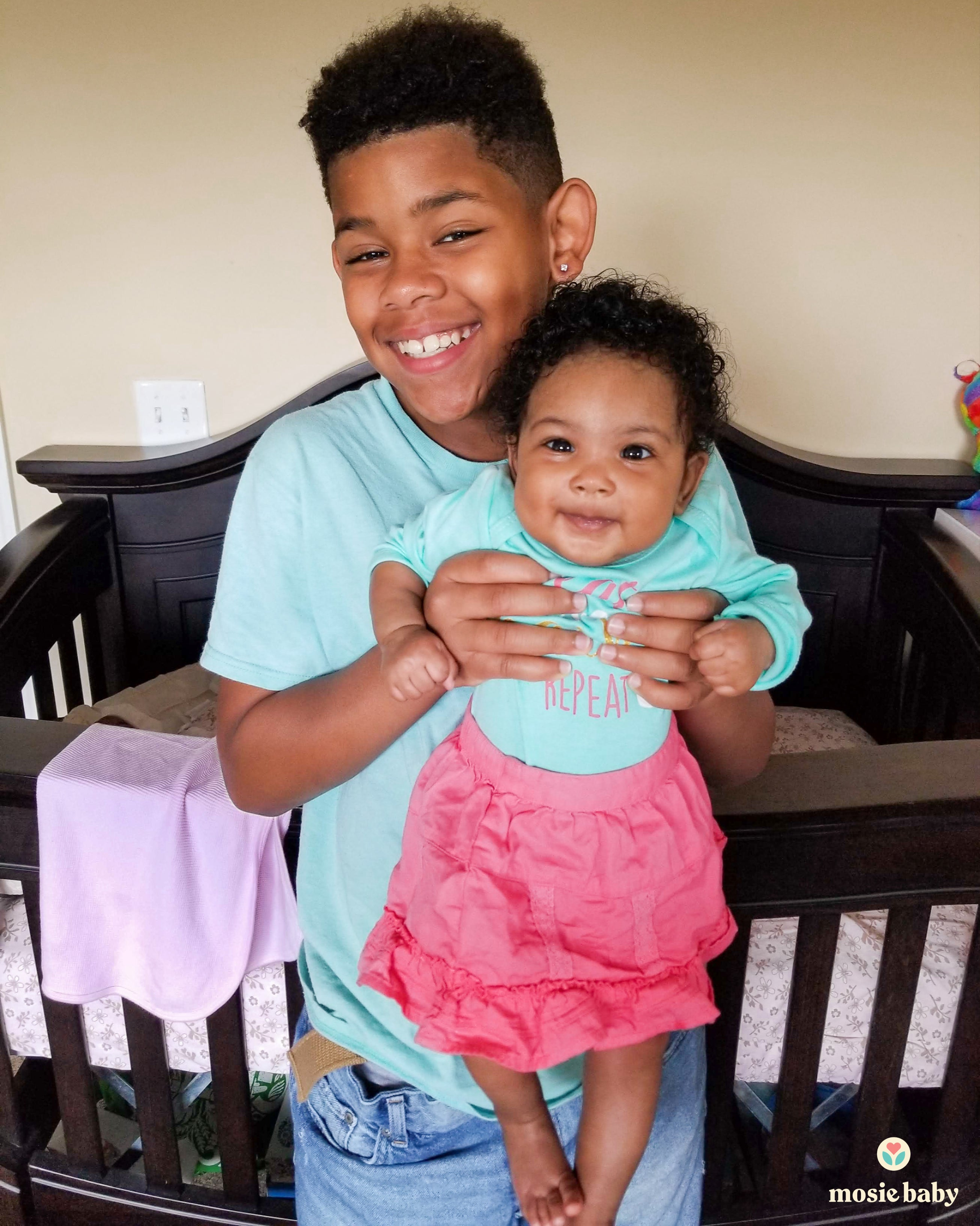 Brother holding his baby sister up and smiling