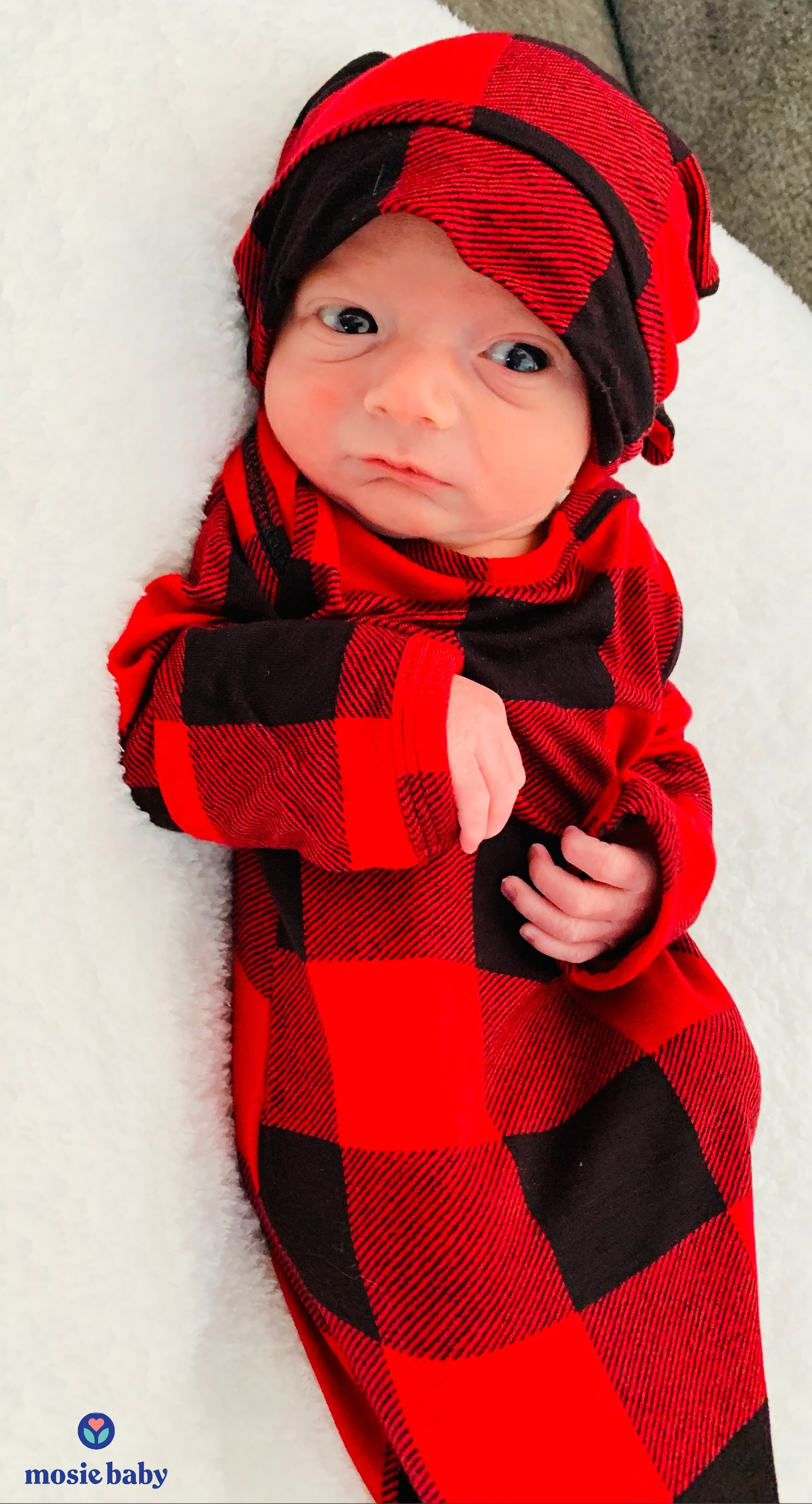 newborn mosie baby in a plaid outfit