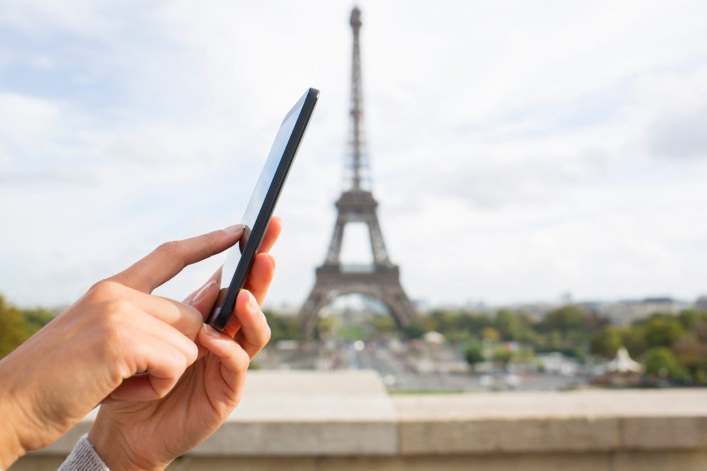 Woman using her cell phone in front of Eiffel Tower