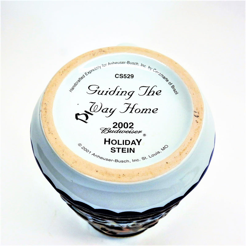 "Bottom view of stein with writing ""CS529 Guiding The Way Home 2002 Budweiser Holiday Stein"""