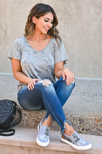 Weekend Wait Burnout Top - Grey Women's grey burnout top featuring rounded v-neckline, short sleeves, side split hem design, and raw edge detailing. Semi-sheer closet candy sitting
