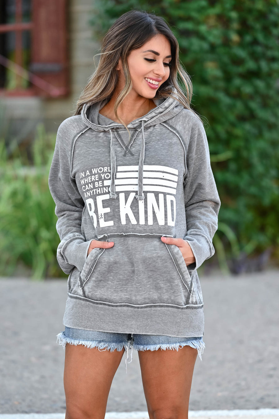 "Be Anything Be Kind Graphic Hoodie - Vintage Grey women's fleece-lined hoodie featuring drawstring hood, reverse stitching detail at neckline, kangaroo pocket, banded cuffs and hem, exposed raw edge seams, and ""In A World Where You Can Be Anything, Be Kind"" graphic on front closet candy sitting"