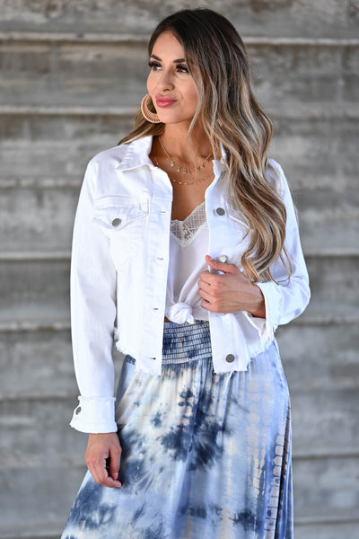 Own It Denim Jacket W/ Raw Hem - White Women's white denim jacket featuring basic collar, long sleeves, raw hem design, button closure at front and cuffs, and chest pockets with flap button closure closet candy close up