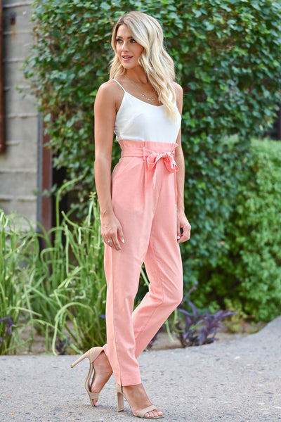 Girl's Getaway Jumpsuit - Coral Coral and ivory jumpsuit with scoop neckline, adjustable spaghetti straps, and side pockets. Bow can be tied in the front or back closet candy side