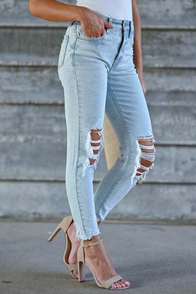 Peyton Cropped Distressed Jeans - Light Wash women's distressed jeans featuring cropped length, distressed raw hem, classic 5-pocket design, and zipper fly with button closure closet candy side