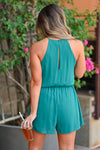 LUSH Still Be Here Romper - Teal Green women's trendy woven romper featuring halter neckline with keyhole cutout detail, plunging front opening, surplice bodice, and elastic waistband. Keyhole cutout with button closure at back closet candy back