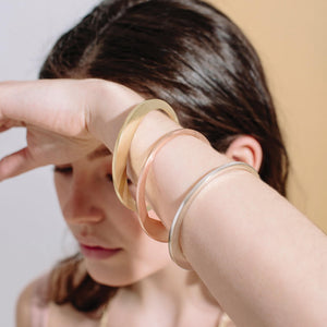 Three uneven circle bangles come together with subtle accents that mold together effortlessly.