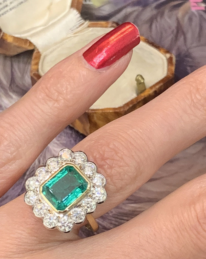 Regal emerald and diamond cluster ring