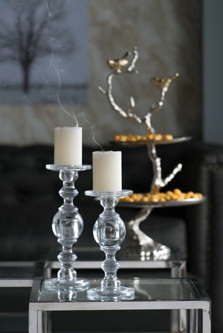 transparent artistic candle holders displayed next to a three tier cake tray with silver branch